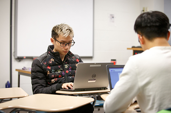 A student works on his computer during a class at Saint Michael's College.